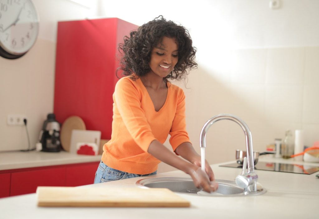 woman in the kitchen washing hands using sink