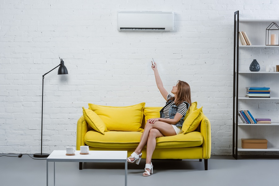 attractive young woman sitting on sofa and pointing at air conditioner with remote control
